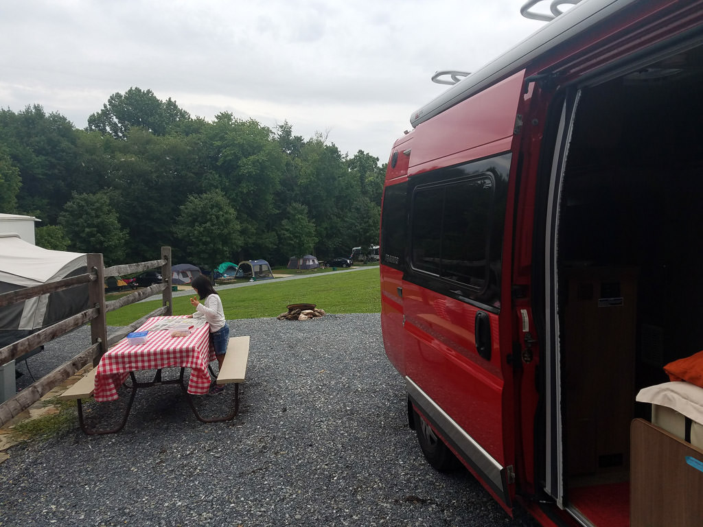 Winnebago Travato parked at campground with side door open and picnic table right out front