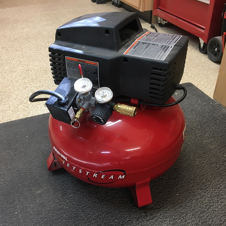 Pancake air compressor sitting on the floor.