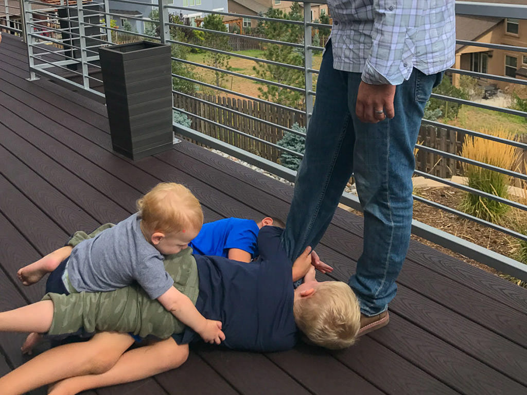 Kids playing together on a deck.