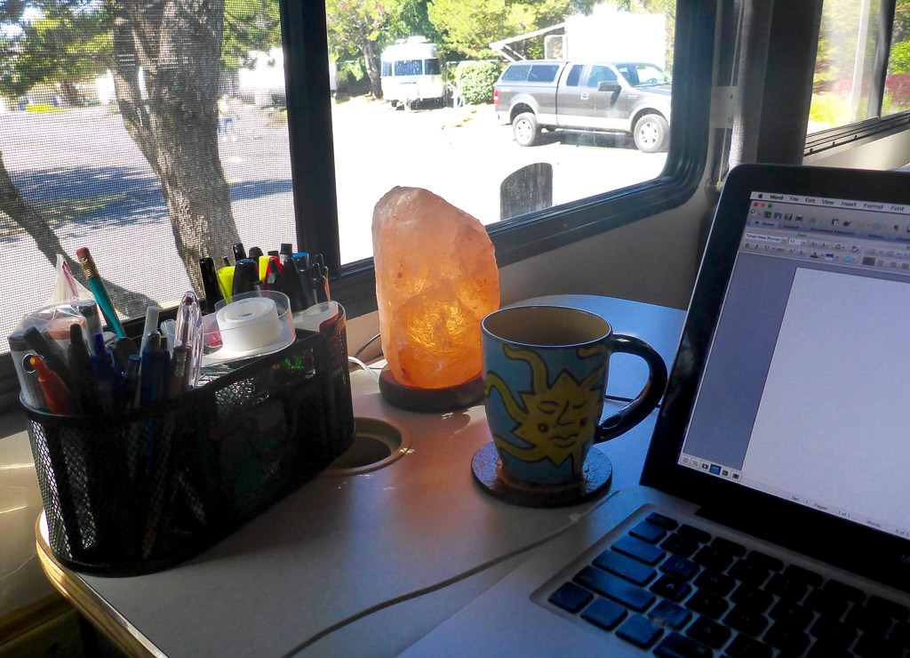 Pencil holder, lamp, coffee mug, and computer on RV dinette.