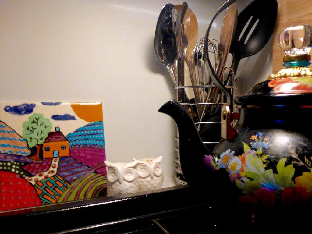 Kitchen utensils, a tea pot and artwork near stovetop.