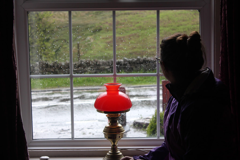 Woman looking out a window to rainy scenery.