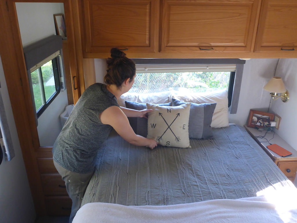 Woman putting a decorative pillow on bed.