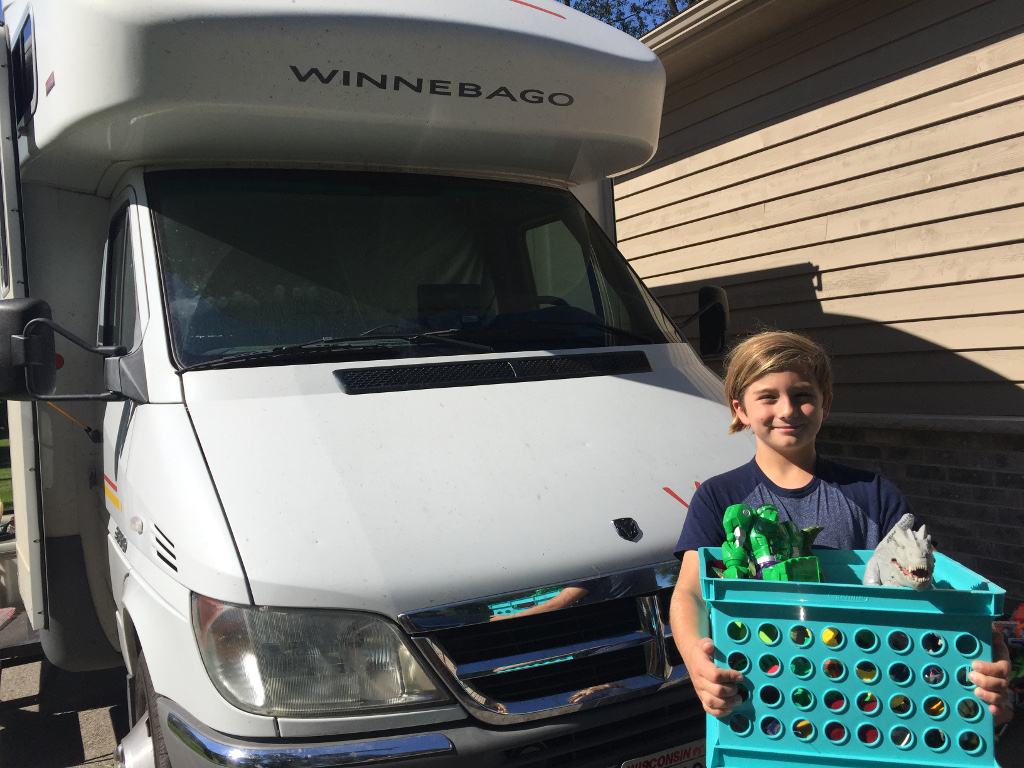 Carson standing in front of Winnebago View holding basket of toys