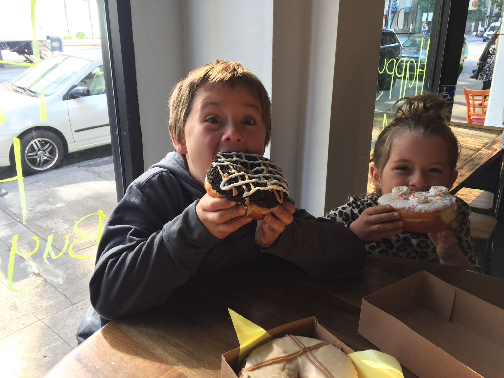 Two of the kids eating huge donuts