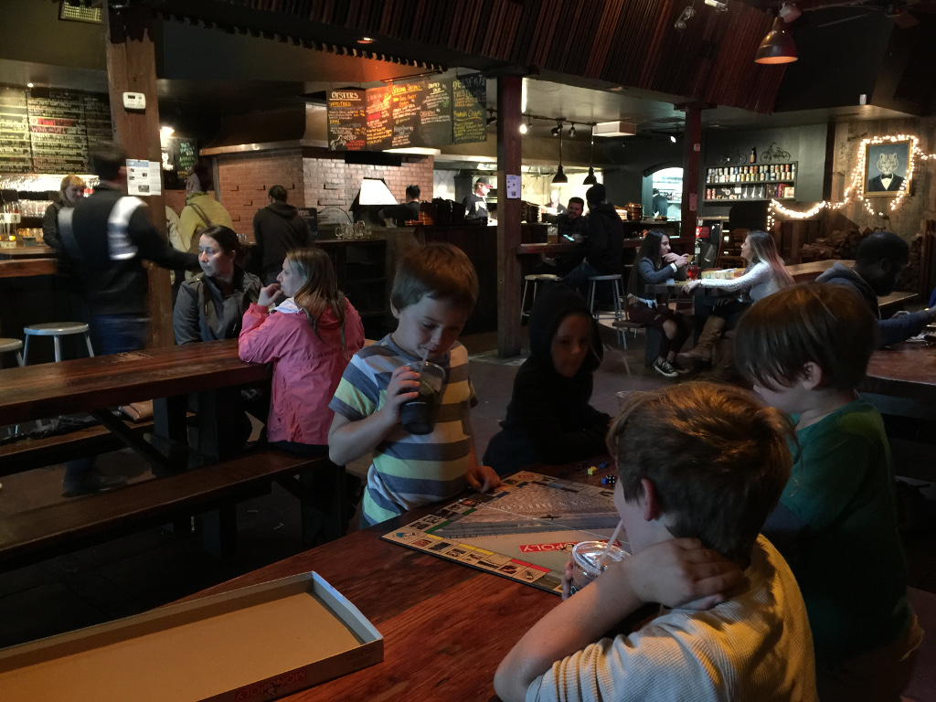 The kids at a table playing Monopoly at a brewery