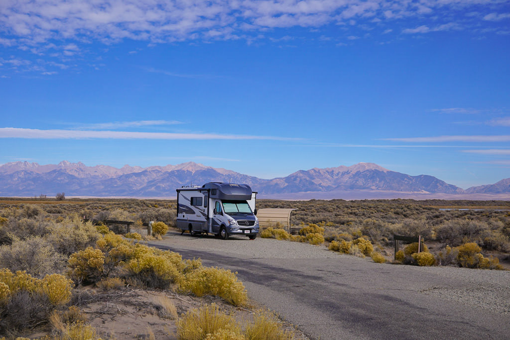 Winnebago Navion parked in campsite with mountains in the background.