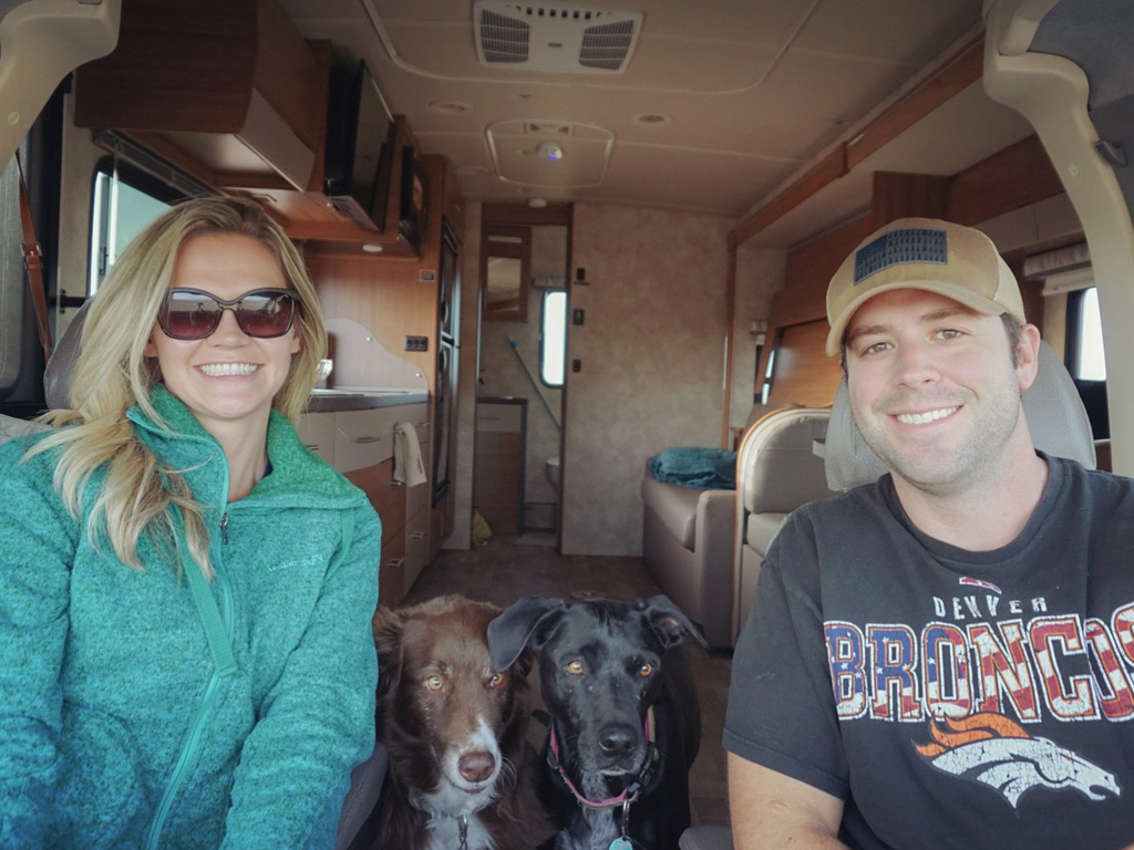Smiling selfie of Dan and Lindsay and their two dogs in their Winnebago Navion.