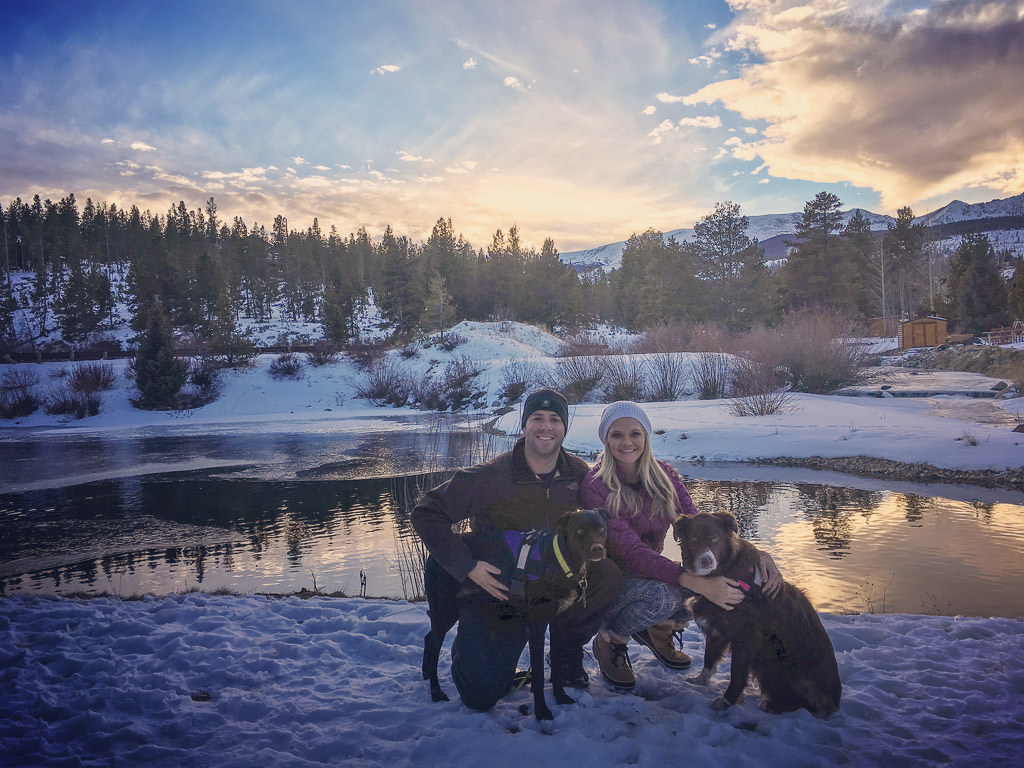 Couple kneeling with their two dogs by a pond with snow covered ground and colorful sky above
