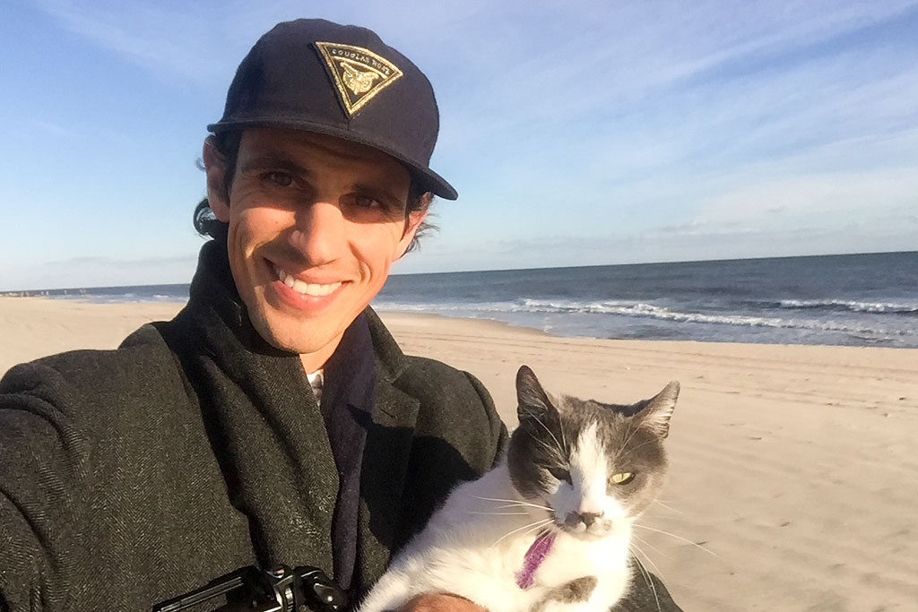Jordan and their cat standing on the beach with ocean in view