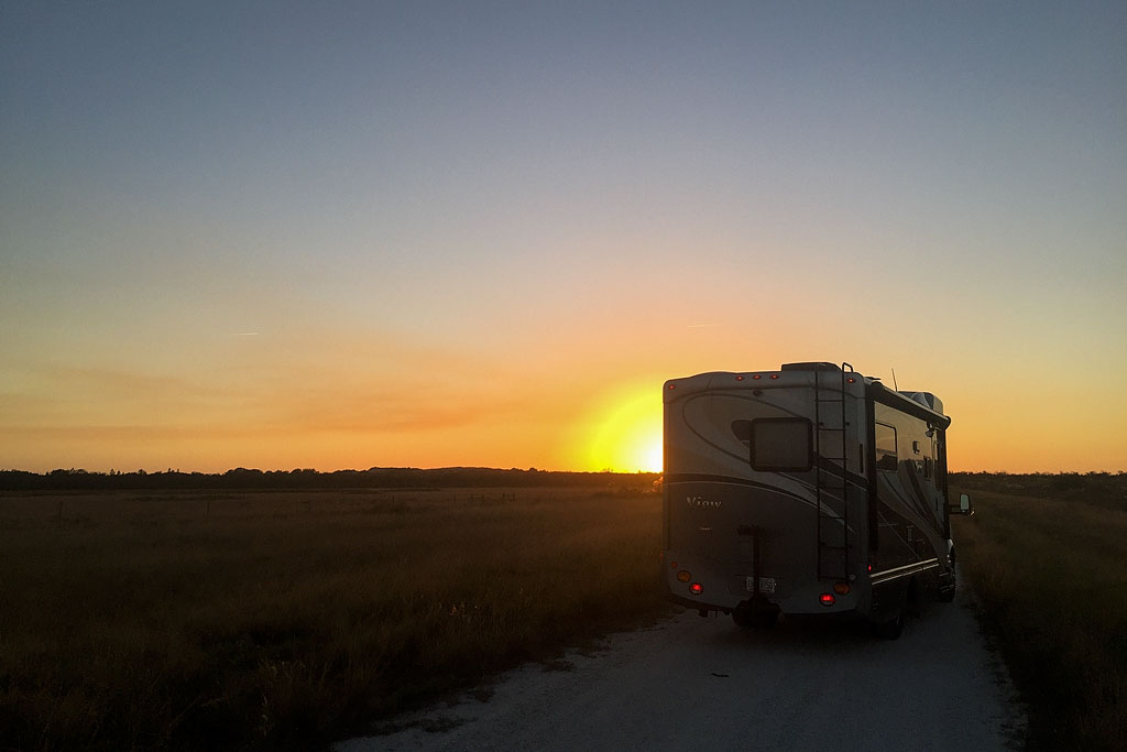 Winnebago View parked on side of the road with sun setting on the horizon