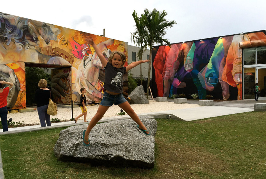 Child jumping off a rock with colorfully painted buildings behind