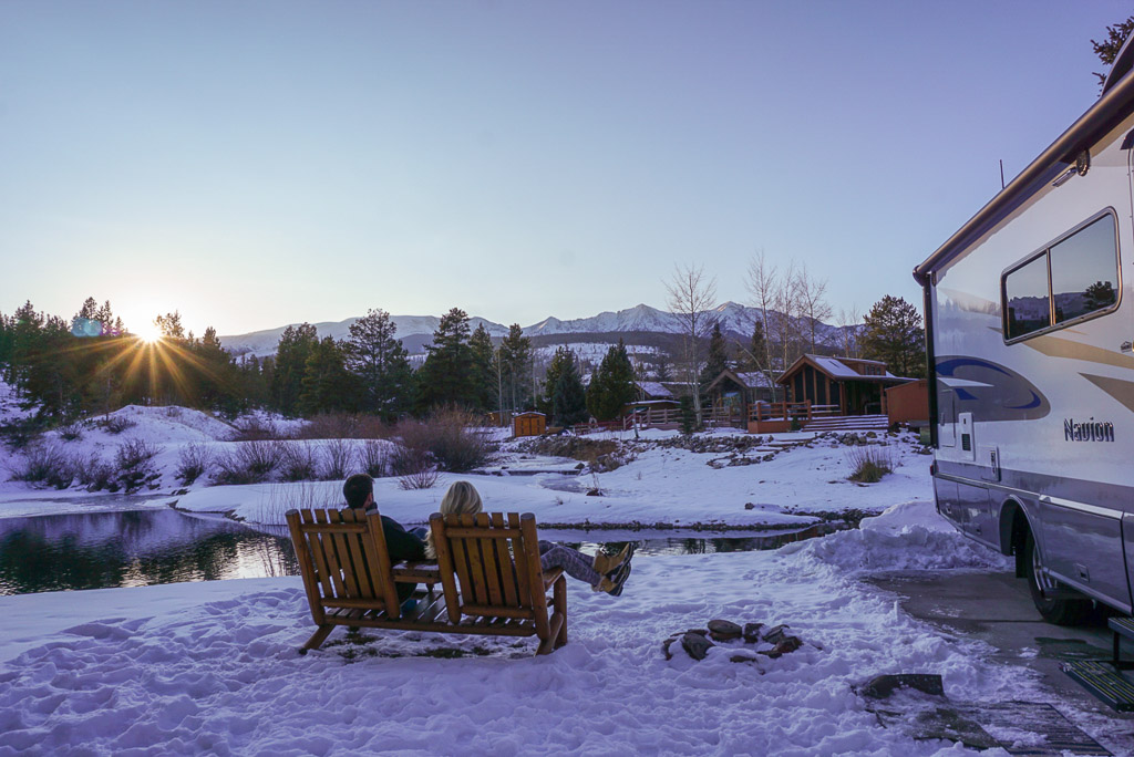 Couple sitting in chairs next to pond with snow covered ground and Winnebago Navion parked to the right