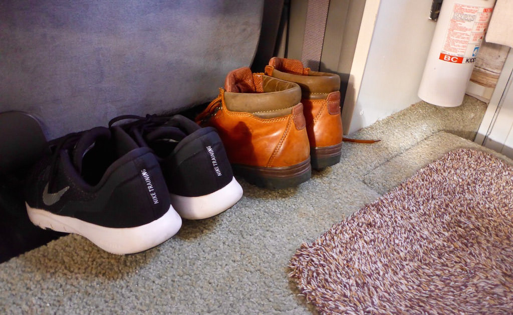 Two pairs of shoes tucked under passenger seat in RV