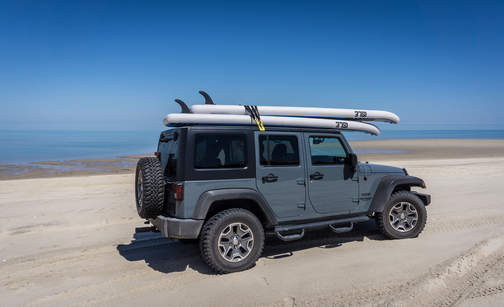 Vehicle parked on the sand with paddle boards on the roof and ocean in the background