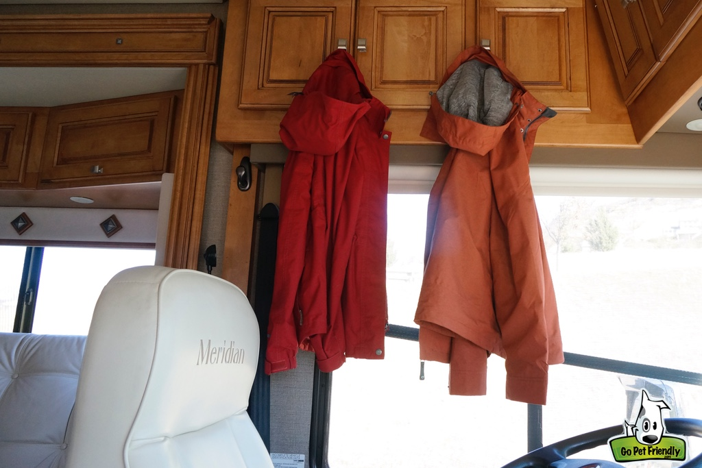 Two rain jackets hanging on cabinets in RV