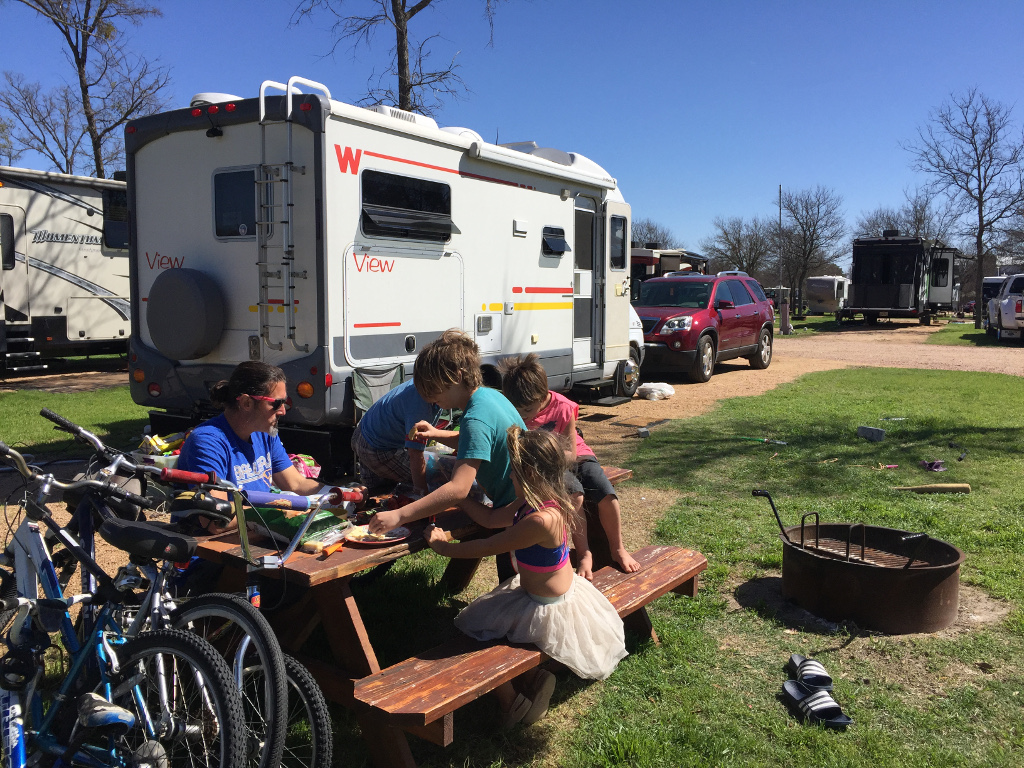 Family sitting at picnic table outside their Winnebago View