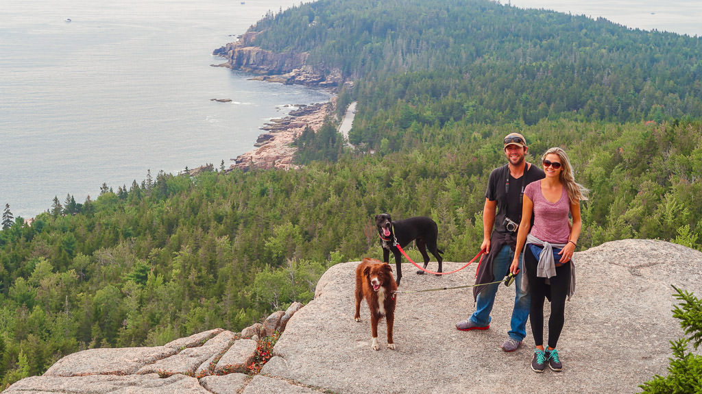 Lindsay, Dan and their two dogs on cliff side with trees and water below