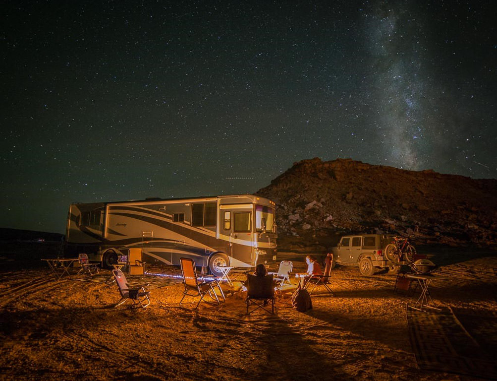 Winnebago Journey parked in rough landscape with stars overhead and campfire roaring