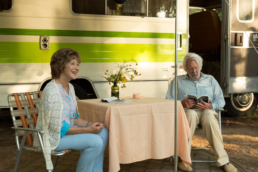 Two characters sitting outside Winnebago Indian onset of the movie