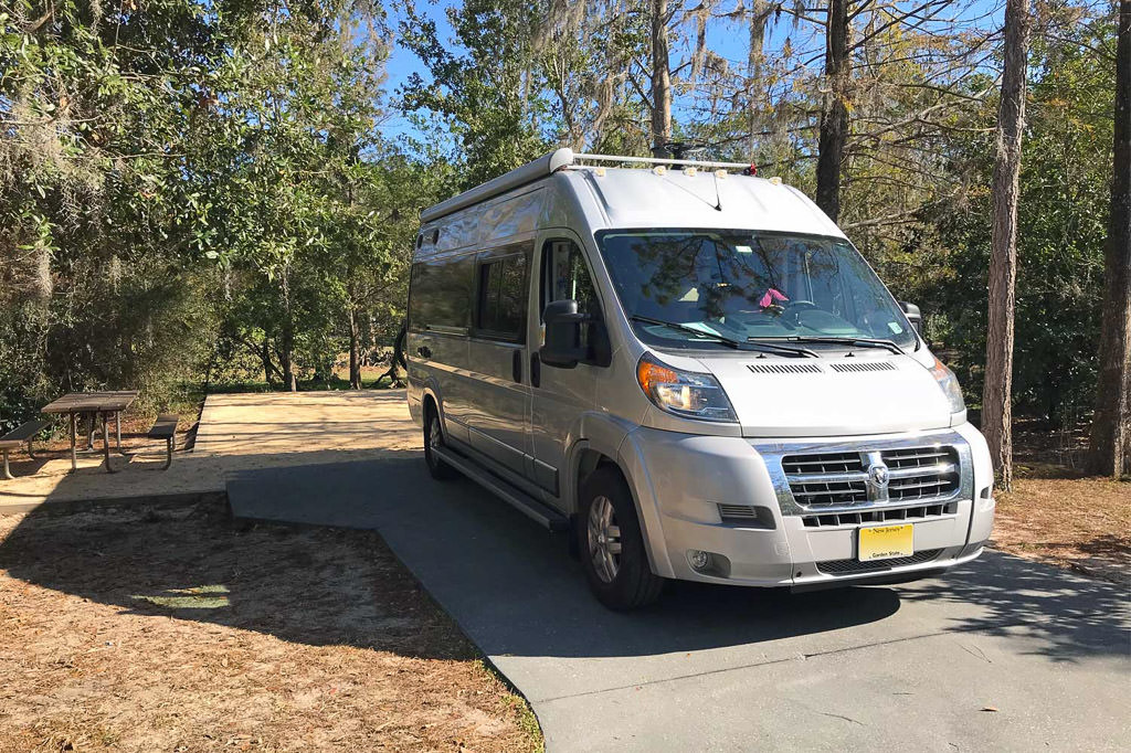RV on paved site with picnic bench in campground