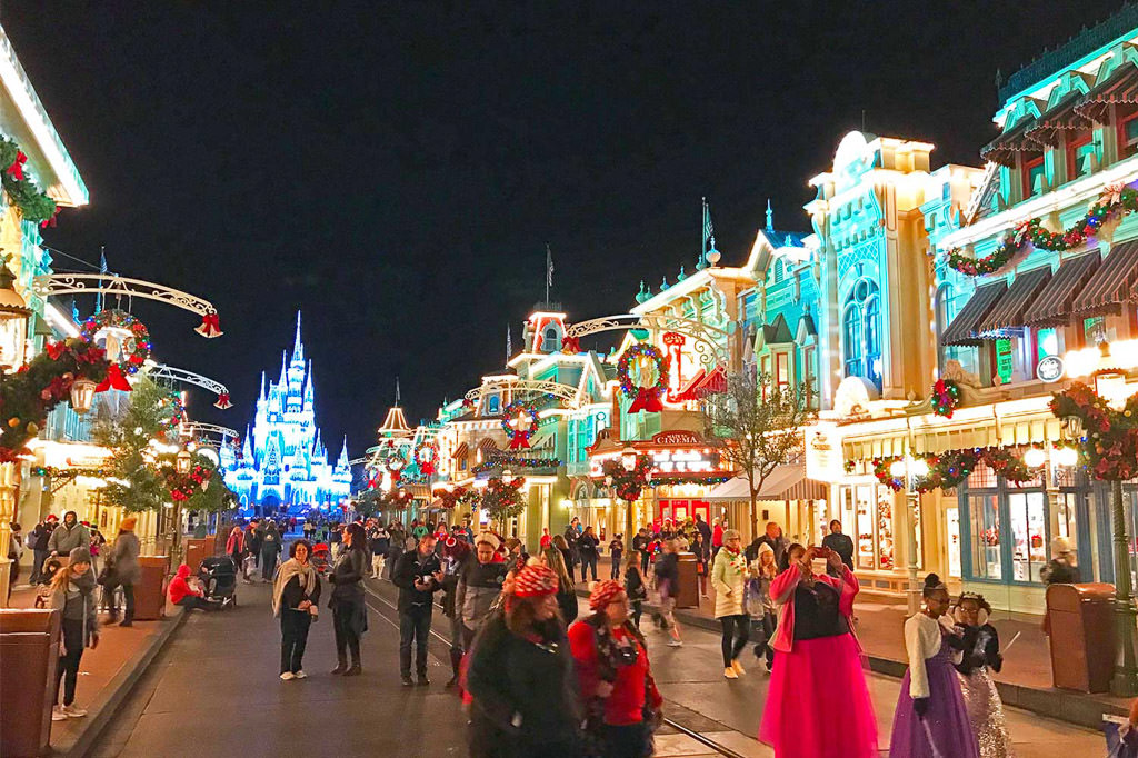 Main walkway in Disney World with castle in background and people dressed for Christmas