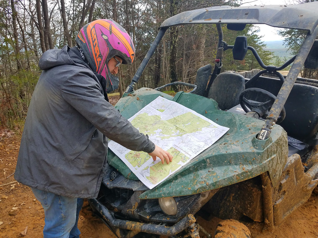 Man looking at a map resting on front end of muddy ATV
