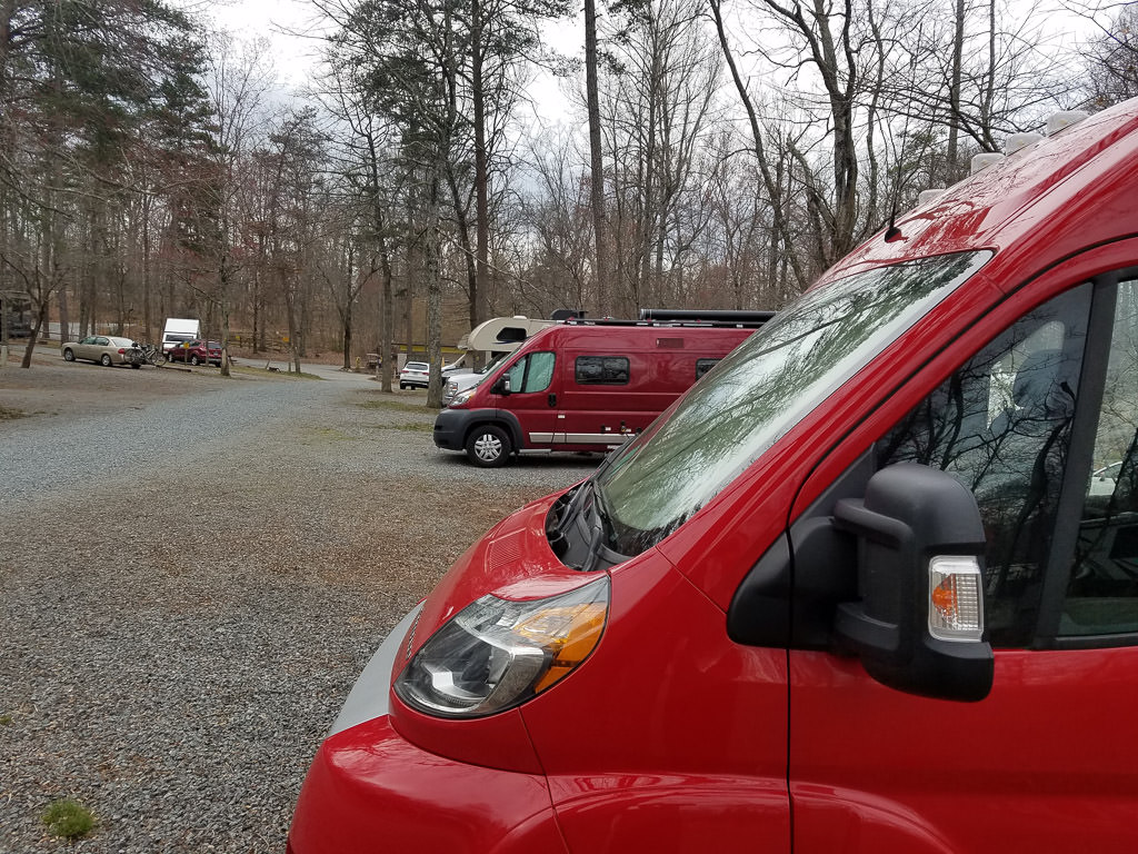 Two red Winnebago Travatos parked at a campground
