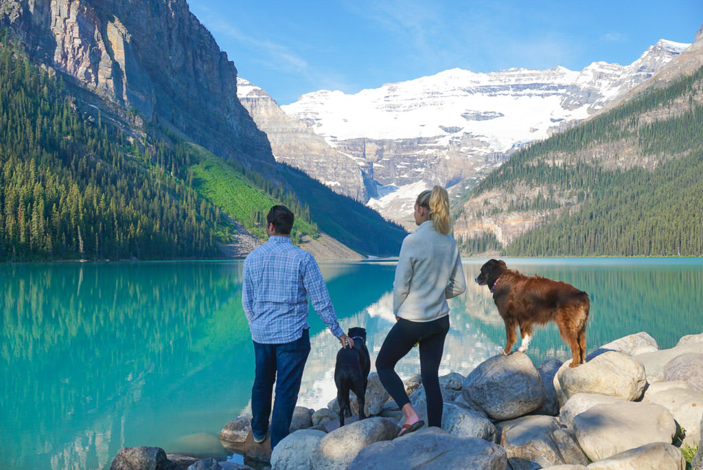 Lindsay and Dan with their two dogs looking out over the lake and mountain filled scenery