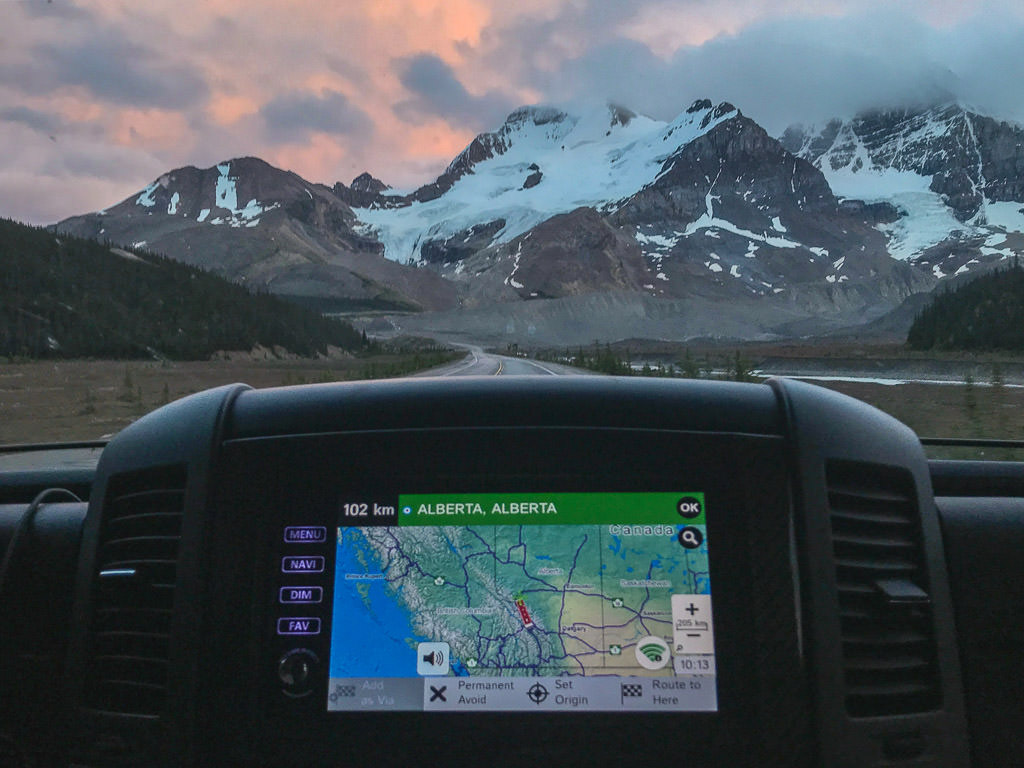 GPS on the RV dash showing Alberta, Alberta with view of mountains out the front windshield