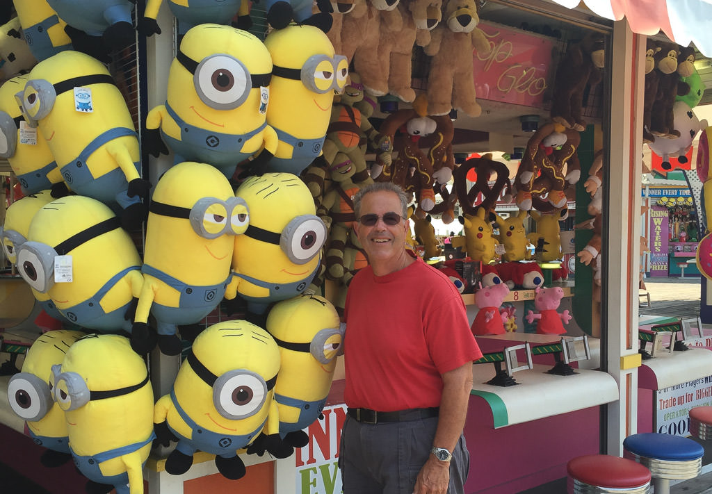 Man posing with carnival stuffed animal prizes