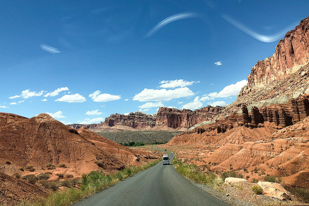 Van driving on road through canyon