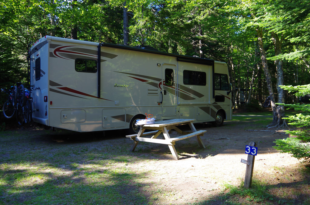 Winnebago Sunstar parked at campsite in campground with picnic bench out front