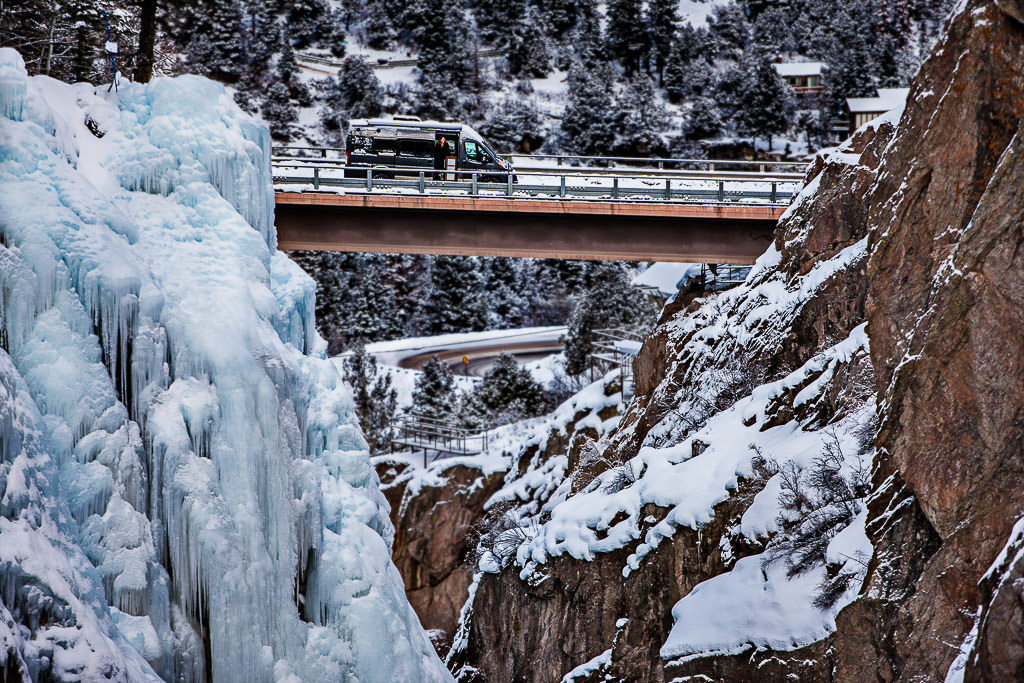 RV parked on a bridge with landscape of ice, snow covered cliffs and trees on either side..