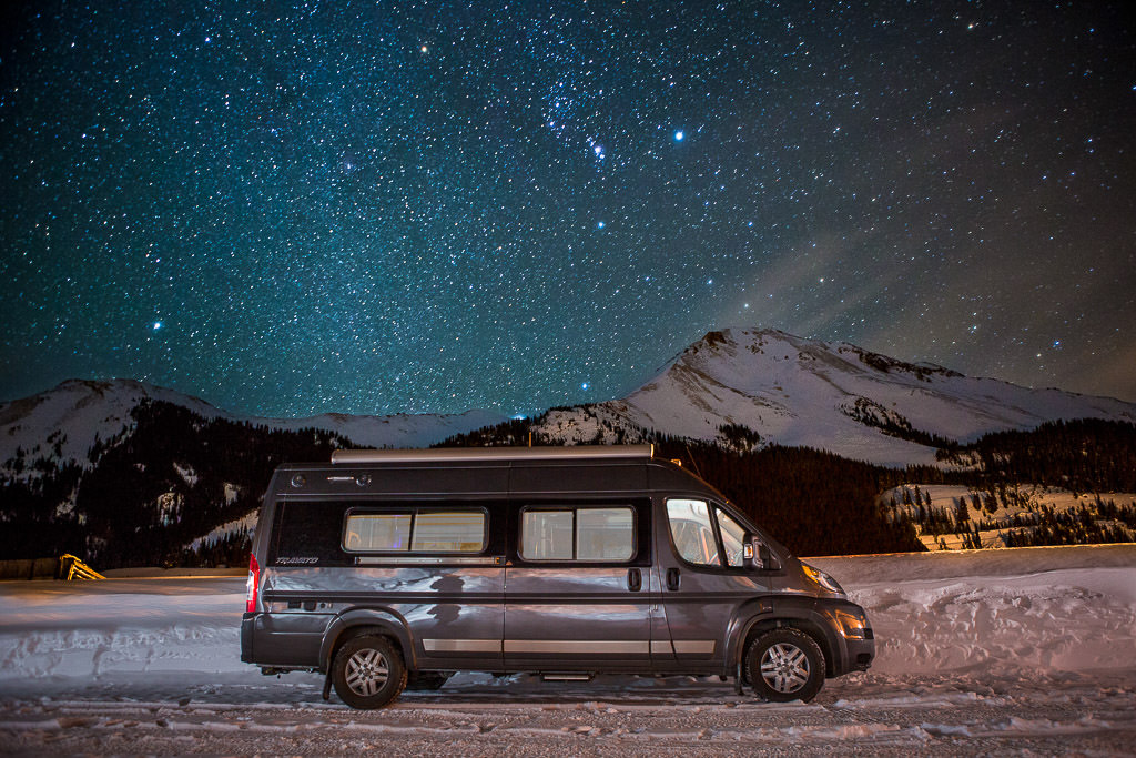 Winnebago Travato parked on snow covered ground with mountains in the background under a star filled night sky.