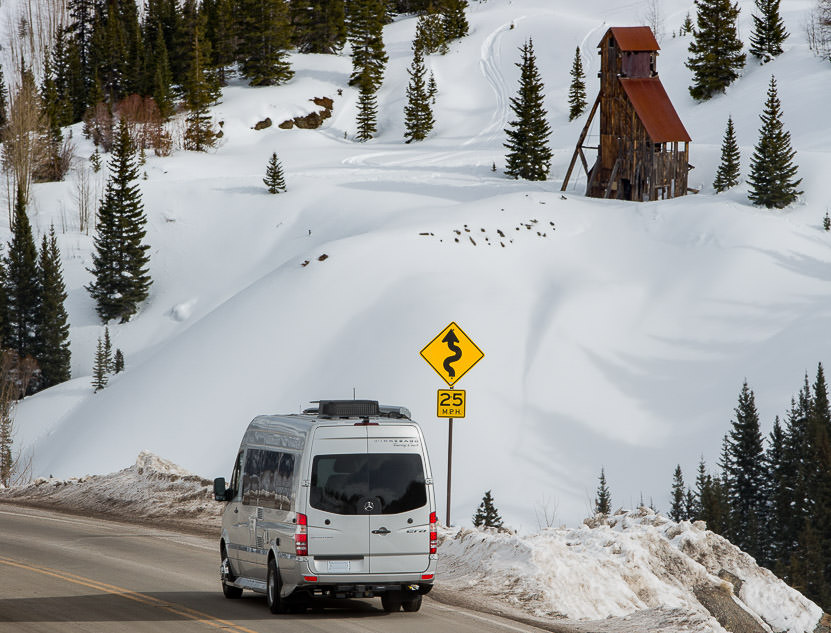 Winnebago Era driving past winding road 25 mph sign with snow covered hillside and evergreens ahead.