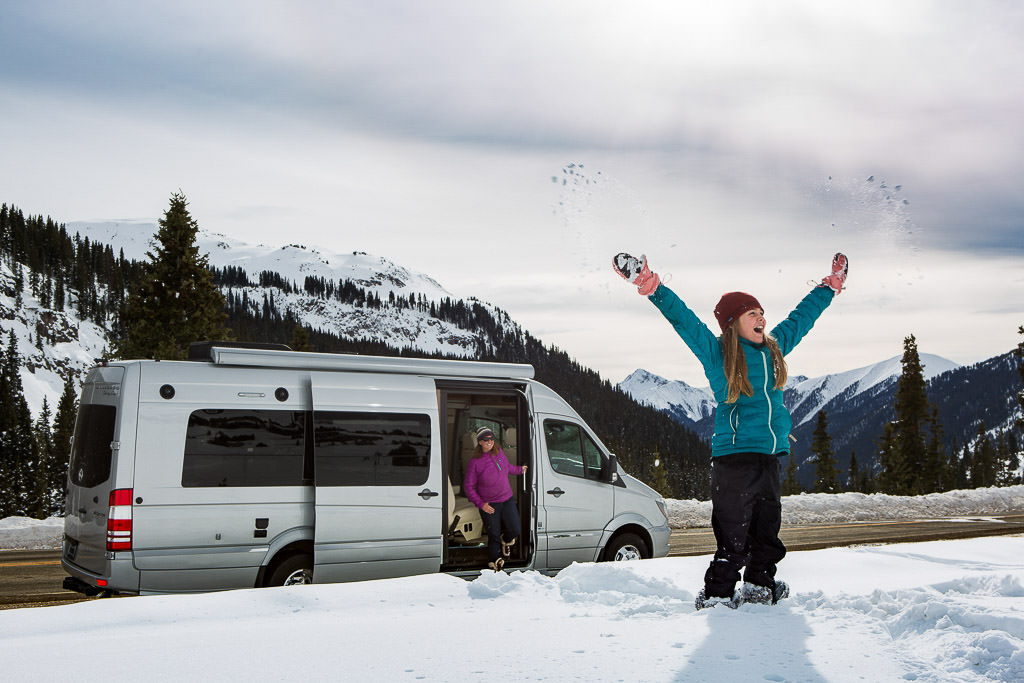 Van parked with snow and tree covered mountains in background, a woman getting out of the van, and a young girl standing in snow throwing snow in the air.