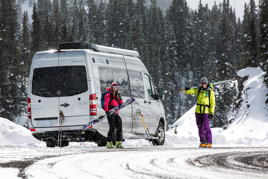Man and woman holding skis standing outside their Winnebago Era parked on snow covered ground.