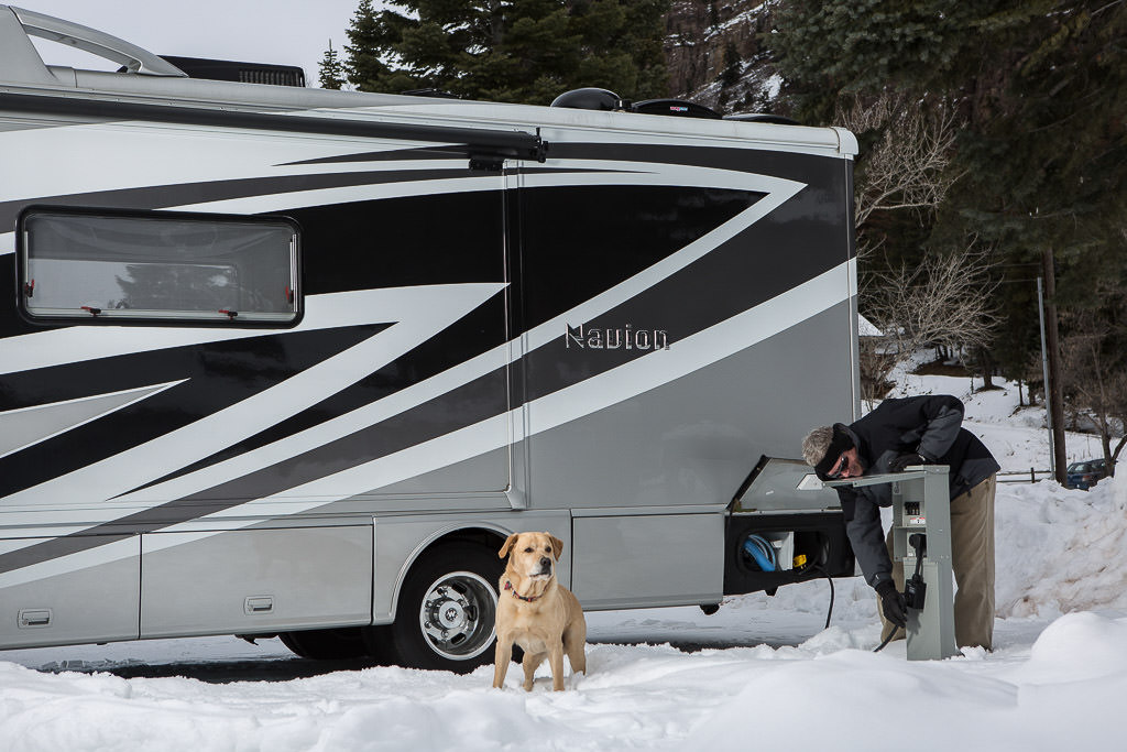 Winnebago Navion parked on snow covered ground with dog outside exploring and man plugging unit in to the electric hook-up.