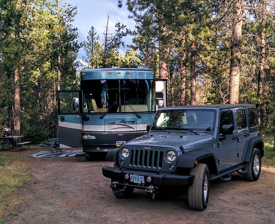 Winnebago Journey and Jeep parked in campsite surrounded by trees.