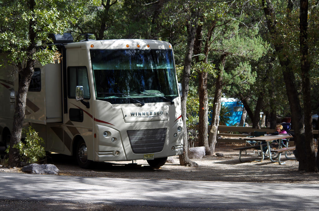 Winnebago motorhome parked at campsite between trees.