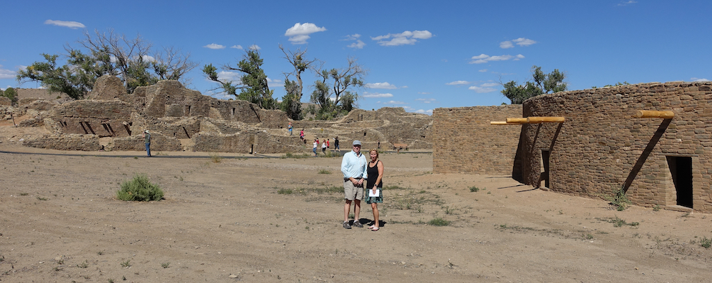 Wider view of Don and his wife standing in front of the ruins his parents were 70 years prior.