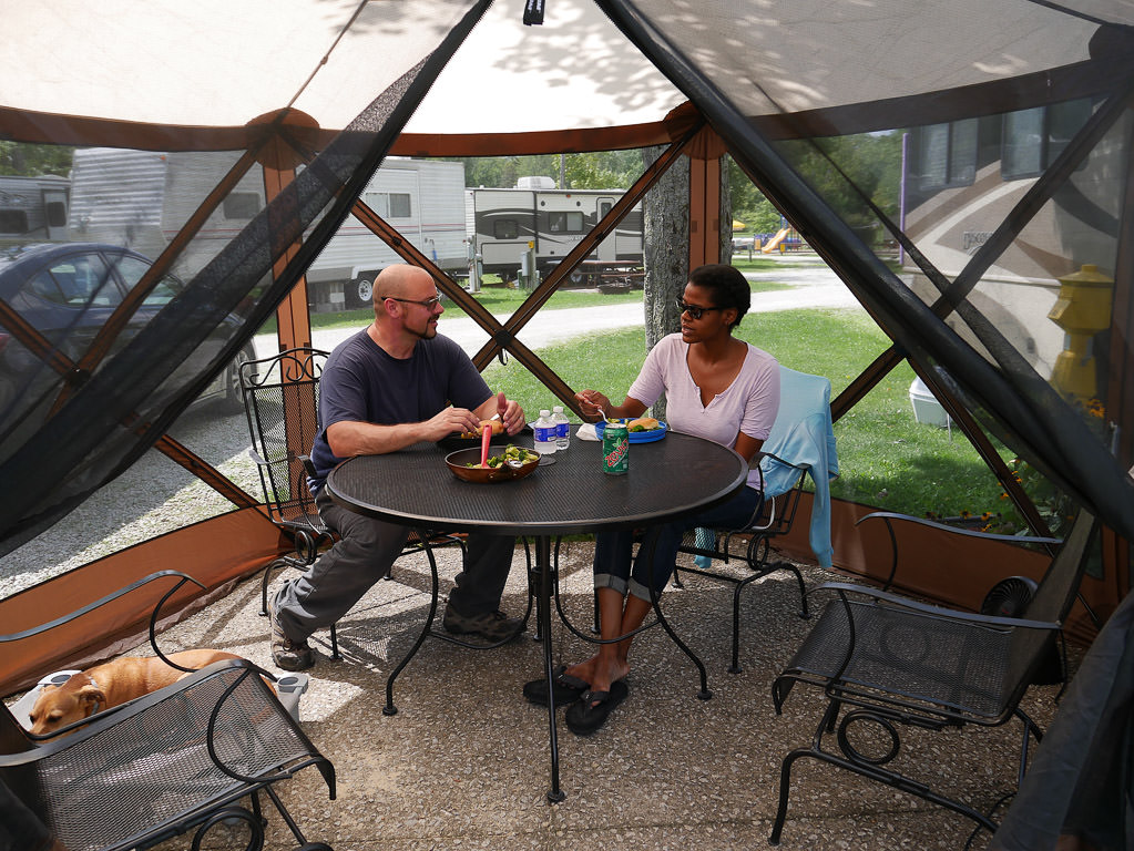 Couple enjoying a meal in their Clam Quick-set escape gazebo