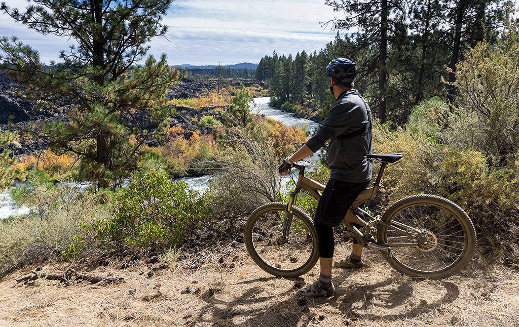 Biker looking out over Deschutes River which is lined with trees.