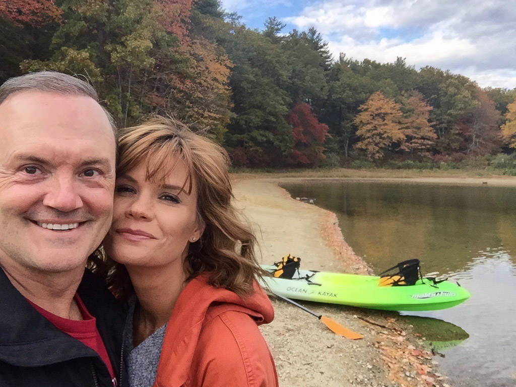 Susan and Bill taking a selfie in front of a lake