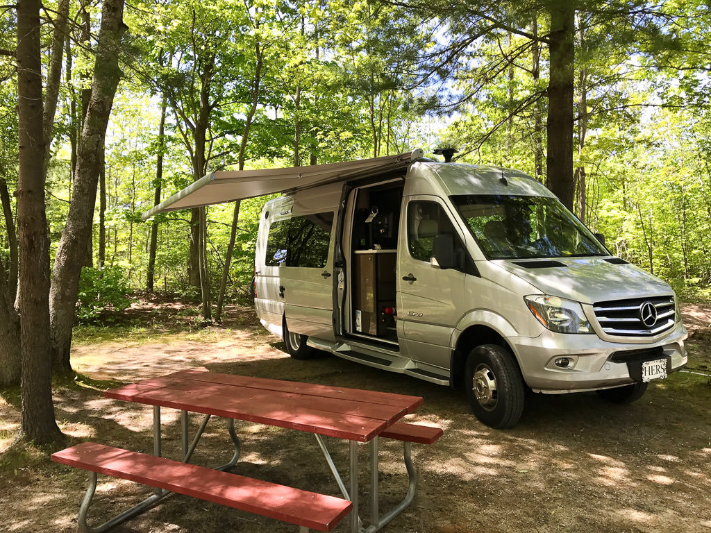 Era parked in campsite with sliding door open and awning out