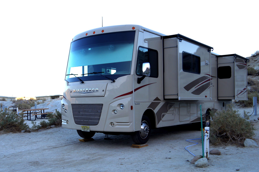 Winnebago Sunstar parked with slide outs out in campsite.