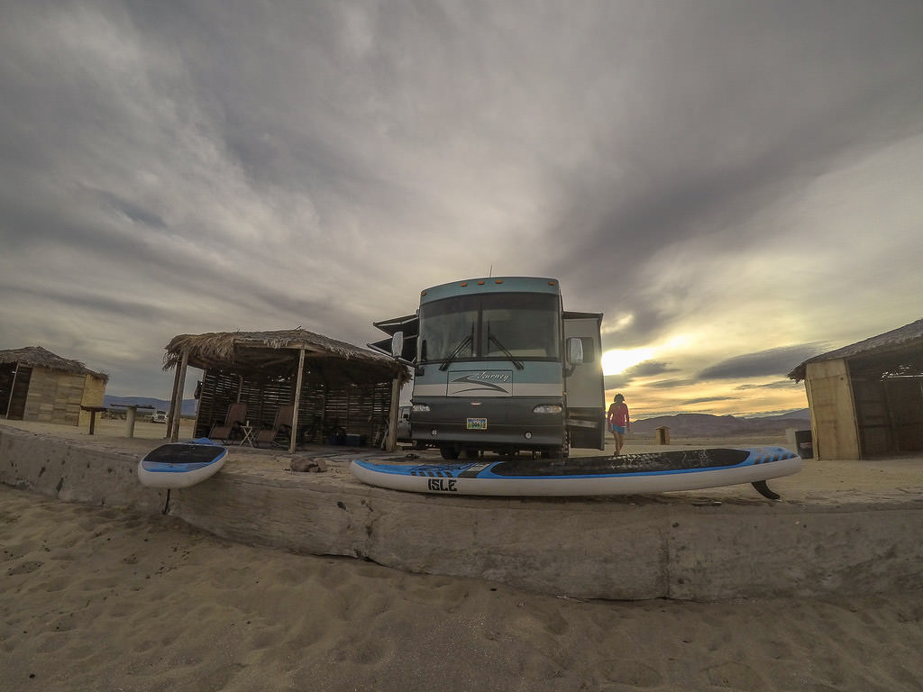 Winnebago Journey parked on sandy campsite with personal palapa and lounge chairs.