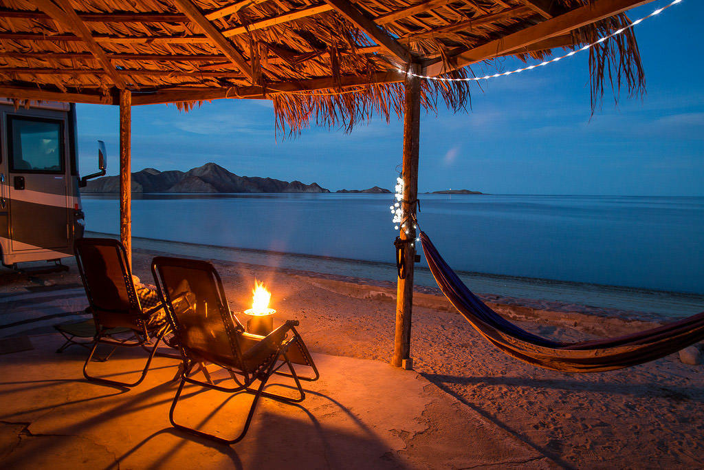 Palapa at the campsite at night with a fire going and a view of the ocean.