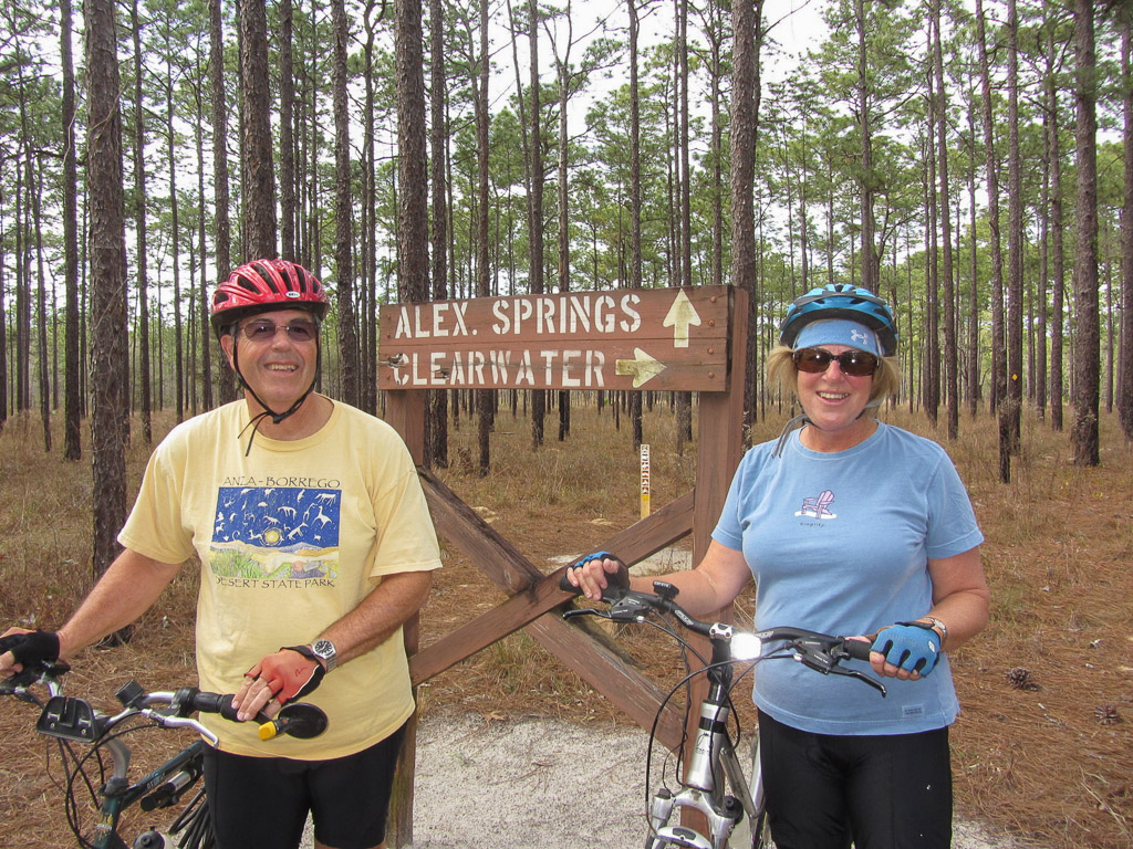 Two people standing with their bikes in front of a sign on the trail for Alex Springs and Clearwater.